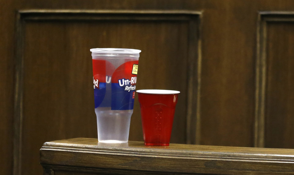 Photo - Two plastic cups are seen on a rail in juvenile court before the start of the third day of the rape trial for Trent Mays , 17, and Ma'lik Richmond, 16, on Friday, March 15, 2013 in Steubenville, Ohio. Defense council used the cups later during testimony to demonstrate the drinking game beer-pong. Mays and Richmond are accused of raping a 16-year-old West Virginia girl in August of 2012. (AP Photo/Keith Srakocic, Pool)
