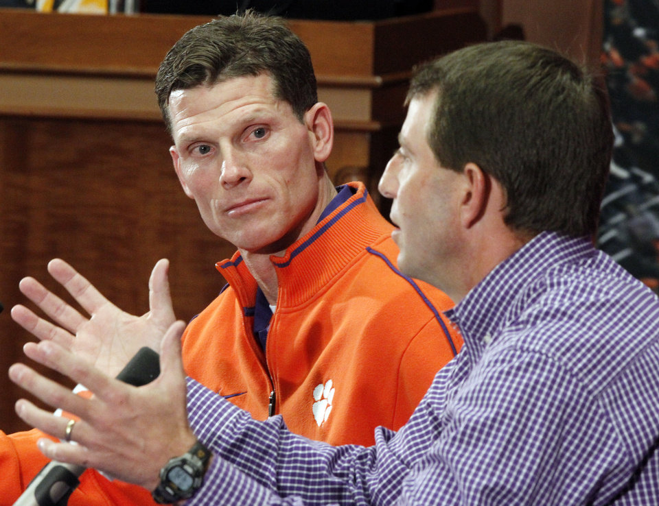 Brent Venables, left, listens as as head coach Dabo Swinney introduces him as the new defensive coordinator at Clemson during an NCAA college football news conference, Friday, Jan. 20, 2012, in Clemson, S.C, (AP Photo/The Independent-Mail, Sefton Ipock) THE GREENVILLE NEWS OUT, SENECA NEWS OUT ORG XMIT: SCAND203