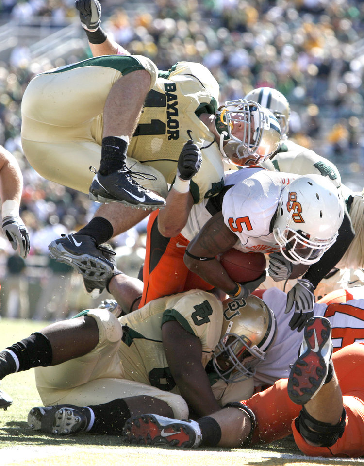 Photo - OSU's Keith Toston (5) scores a touchdown as Baylor's Phil Taylor (11) is up ended during the college football game between Baylor University and Oklahoma State University (OSU) at Floyd Casey Stadium in Waco, Texas, Saturday, Oct. 24, 2009.  Photo by Sarah Phipps, The Oklahoman
