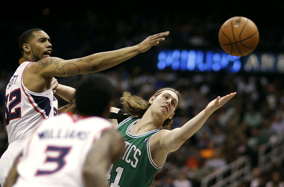 Photo - Boston Celtics' Kelly Olynyk, right, reaches for a rebound against Atlanta Hawks' Mike Scott, left, in the third quarter of an NBA basketball game, Wednesday, April 9, 2014, in Atlanta. (AP Photo/David Goldman)
