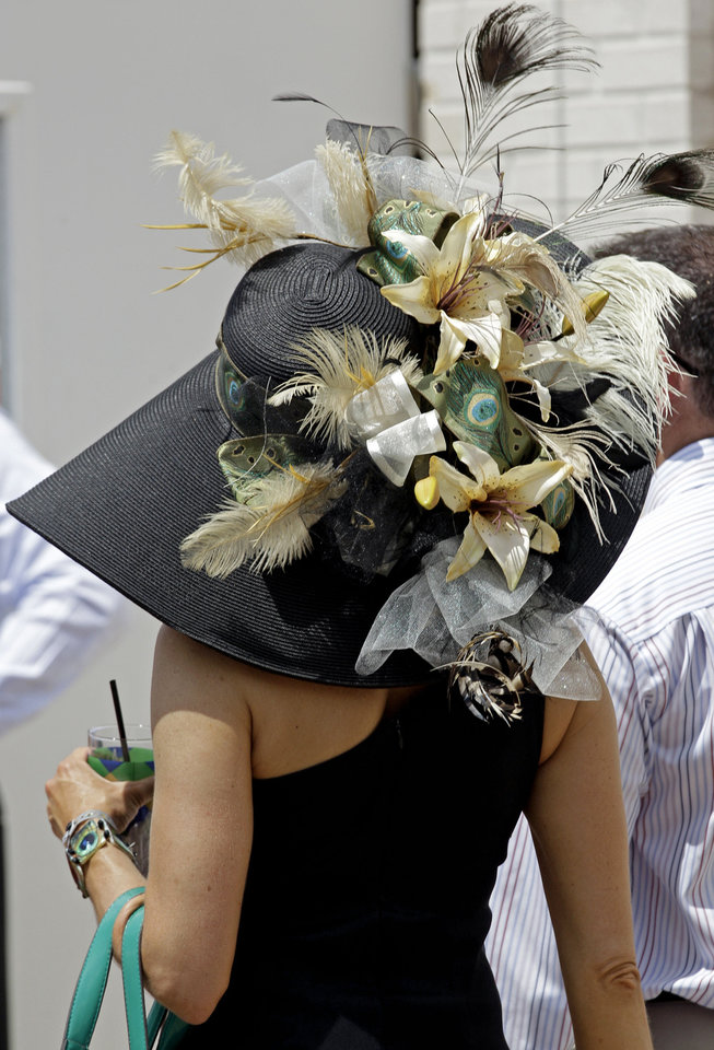 Photo - A spectator walks through the paddock with her fancy hat before the 138th Kentucky Derby horse race at Churchill Downs Saturday, May 5, 2012, in Louisville, Ky. (AP Photo/David J. Phillip)  David J. Phillip - AP