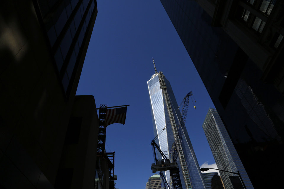 Photo - FILE - This Sept. 22, 2013 file photo shows a partial view of One World Trade Center, a skyscraper built at the site of the 9/11 attacks on the World Trade Center in New York. Soaring above the city at 1,776 feet, 104-story One World Trade Center is in contention with Chicago's Willis Tower for the title of America's tallest building. A committee of architects recognized as the arbiters on world building heights is meeting Friday Nov. 8, 2013 in Chicago to decide whether a design change affecting One World Trade Center's needle disqualifies its hundreds of feet from being counted, which would deny the building the title of nation's tallest giving the title to the 110 story Willis Tower at 1,450 feet. (AP Photo/Lefteris Pitarakis)