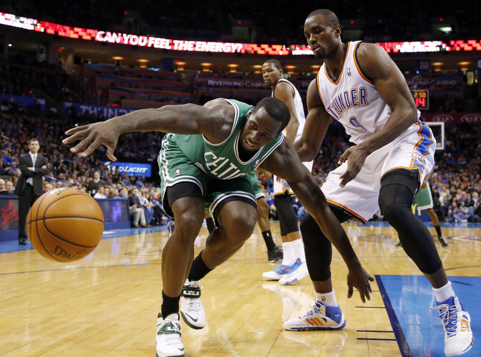 Boston Celtics forward Brandon Bass, left, reaches for the ball in front of Oklahoma City Thunder forward Serge Ibaka (9) in the second quarter of an NBA basketball game in Oklahoma City, Sunday, Jan. 5, 2014. (AP Photo/Sue Ogrocki)