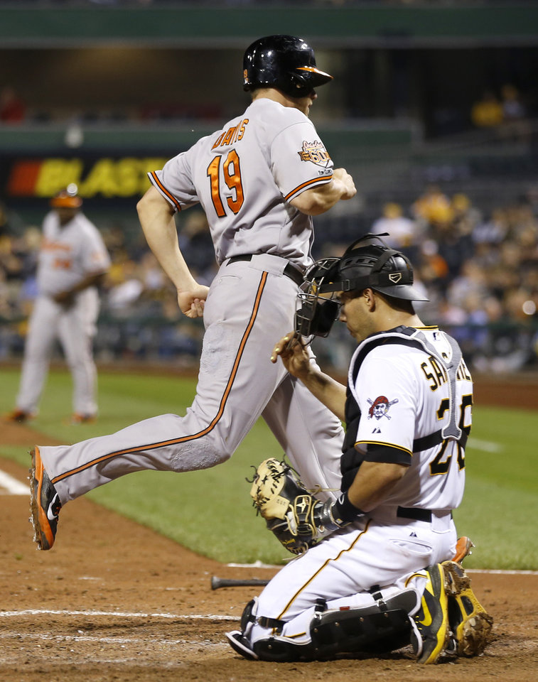 Photo - Baltimore Orioles' Chris Davis (19) scores past Pittsburgh Pirates catcher Tony Sanchez in the seventh inning of a baseball game Wednesday, May 21, 2014, in Pittsburgh. The Pirates won 9-8. (AP Photo/Keith Srakocic)