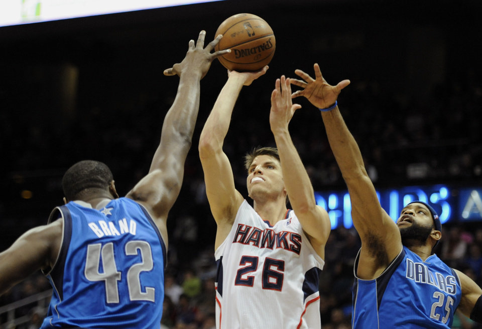 Atlanta Hawks forward Kyle Korver (26), shoots while defended by Dallas Mavericks  forward Elton Brand (42), and guard Vince Carter (25) during the first half of an NBA basketball game, Monday, March 18, 2013, in Atlanta. (John Amis/AP Photo)