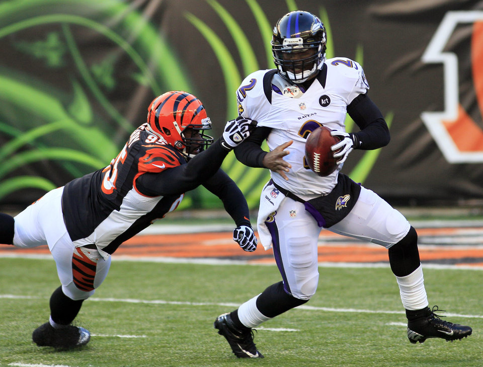 Photo - Baltimore Ravens quarterback Tyrod Taylor (2) is pursued by Cincinnati Bengals defensive end Wallace Gilberry (95) in the second half of an NFL football game, Sunday, Dec. 30, 2012, in Cincinnati. The Bengals won 23-17. (AP Photo/Tom Uhlman)