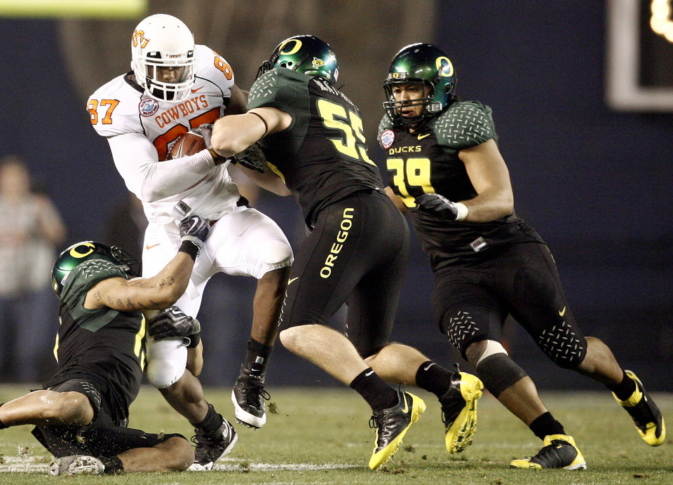 Photo - OSU's Brandon Pettigrew fights off Oregon's Patrick Chung, left, Casey Matthews, and Will Tukuafu  during the Holiday Bowl college football between Oklahoma State and Oregon at Qualcomm Stadium in San Diego, Tuesday, Dec. 30, 2008.  PHOTO BY BRYAN TERRY, THE OKLAHOMAN.