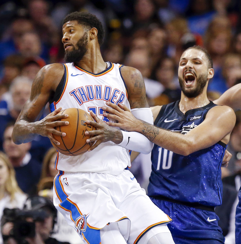 Photo - Oklahoma City's Paul George (13) spins away from Orlando's Evan Fournier (10) during an NBA basketball game between the Oklahoma City Thunder and the Orlando Magic at Chesapeake Energy Arena in Oklahoma City, Monday, Feb. 26, 2018. Oklahoma City won 112-105. Photo by Nate Billings, The Oklahoman