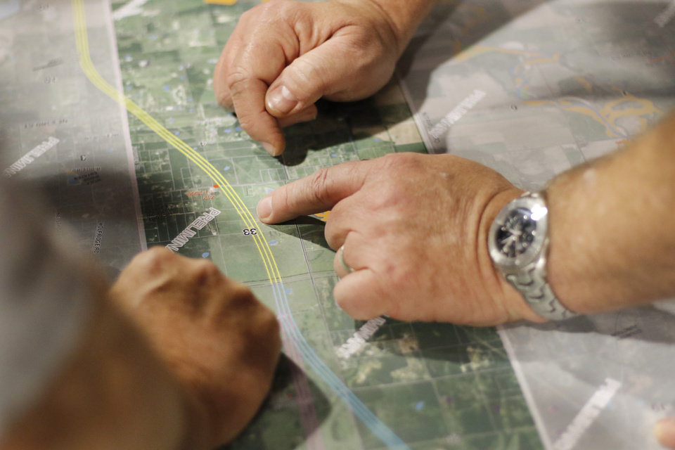 Photo - People pinpoint their property on the map during the Oklahoma Turnpike Authority (OTA) release of the preliminary map for the proposed new eastern Oklahoma county turnpike in Harrah, Thursday, March 10, 2016. Photo by Doug Hoke, The Oklahoman