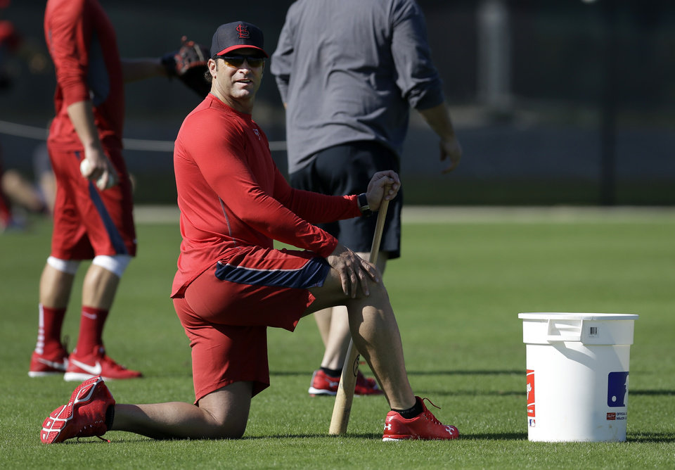 Photo - St. Louis Cardinals manager Mike Matheny takes a knee as he watches his team during an informal spring training baseball practice Wednesday, Feb. 12, 2014, in Jupiter, Fla. Cardinals pitchers and catchers first official practice is scheduled for Thursday. (AP Photo/Jeff Roberson)