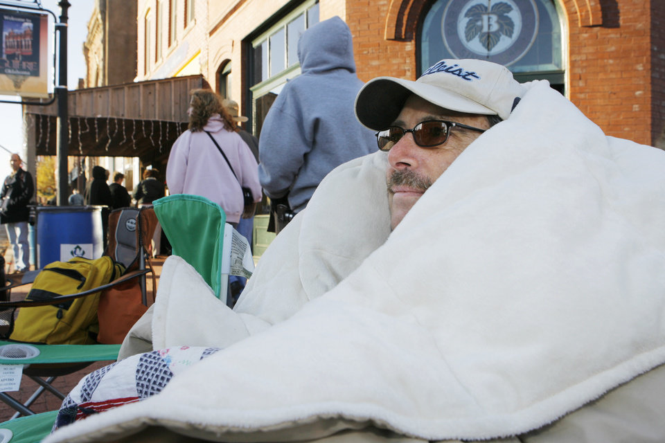 Photo - Terry Hamilton, from Cedar Valley, stake out his spot at 7:00 a.m. on the parade rout and brought plenty of blankets for the could, Friday, November 16, 2007.  By David McDaniel, The Oklahoman