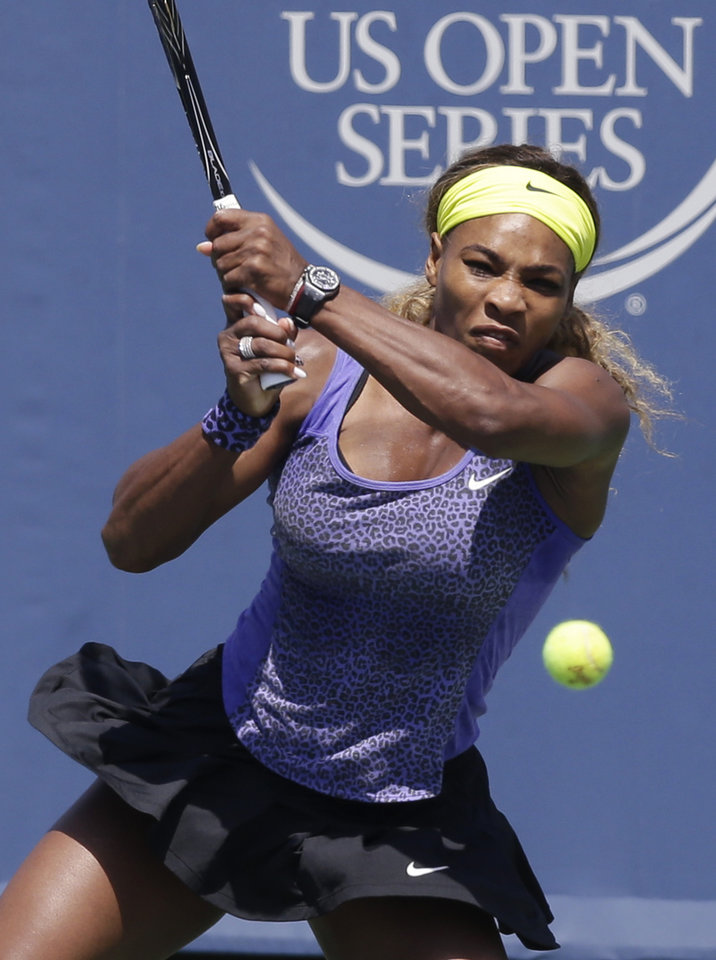 Photo - Serena Williams hits a backhand against Jelena Jankovic, from Serbia, during a match at the Western & Southern Open tennis tournament, Friday, Aug. 15, 2014, in Mason, Ohio. (AP Photo/Al Behrman)
