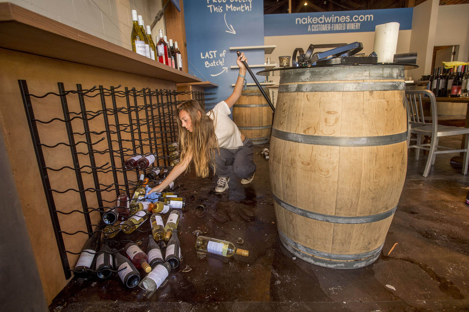 Photo - Grace Hardy cleans up wine bottles at nakedwines.com in Napa, Calif., following an earthquake Sunday, Aug. 24, 2014. Winemakers in California's storied Napa Valley woke up to thousands of broken bottles, barrels and gallons of ruined wine as a result of Sunday's earthquake. (AP Photo/Noah Berger)