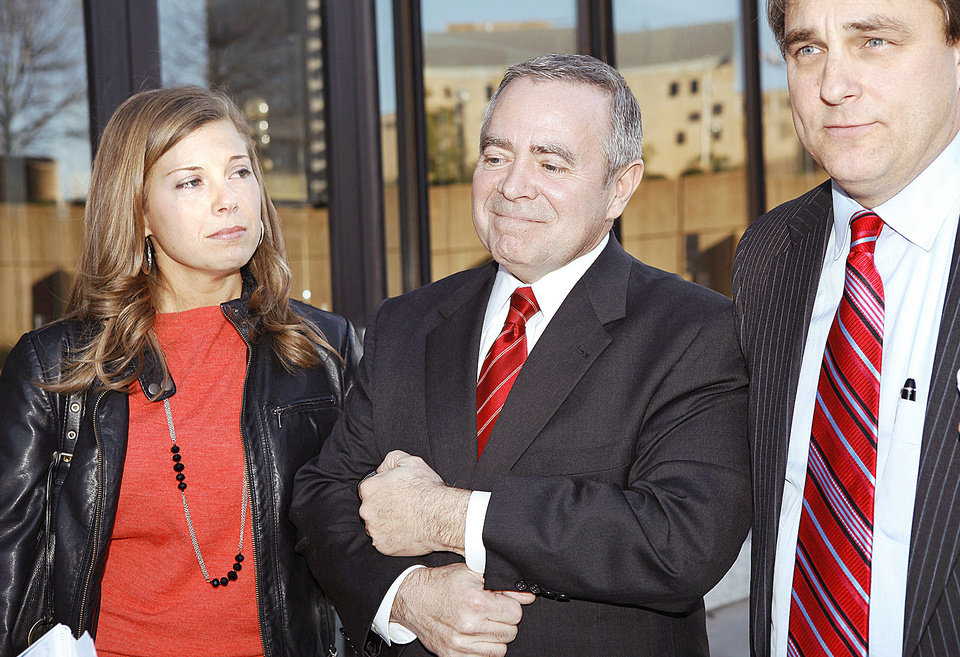 Photo - Former state Senate leader Mike Morgan holds the arm of his daughter, Abby, as defense attorney, David Ogle, tells reporters Monday that they will appeal his bribery conviction. Photo by Jim Beckel, The Oklahoman