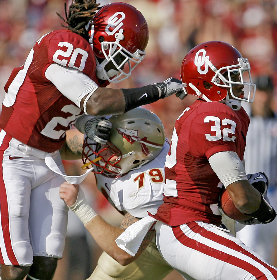 Photo - OU's Jamell Fleming intercepts the ball in front of Flordia State's David Spurlock and OU's Quinton Carter during the second half of the college football game between the University of Oklahoma Sooners (OU) and Florida State University Seminoles (FSU) at the Gaylord Family-Oklahoma Memorial Stadium on Saturday, Sept. 11, 2010, in Norman, Okla.   Photo by Bryan Terry, The Oklahoman