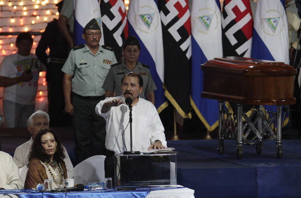 Photo -   FILE - In this May 2, 2012 file photo, Nicaragua's President Daniel Ortega speaks during a midnight funeral of the late Tomas Borge, the last surviving founder of the Sandinista guerrilla movement, in Managua, Nicaragua. At left is first lady Rosario Murillo. Borge, the country's powerful interior minister from 1979 to 1990 and Sandinista hard-liner died on April 30 at age 81 after being hospitalized for pneumonia and other ailments. In death, Borge has been given near-saint status by Ortega and his wife. Critics suggest they are using the mourning to bolster the legitimacy of a government whose last election was widely questioned. (AP Photo/Arnulfo Franco, File)