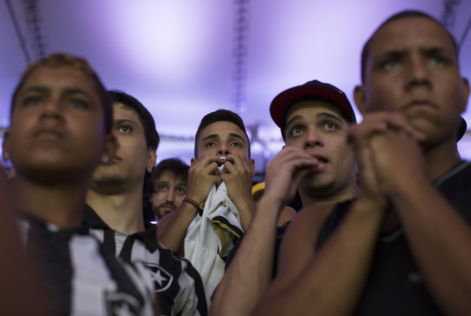 Photo - In this April 2, 2014 photo, fans of the Botafogo soccer team watch a Copa Libertadores soccer match at Maracana stadium in Rio de Janeiro, Brazil. Soccer's big moment happens in June as the best players on the planet meet in Brazil for the World Cup. In Brazil, soccer is a unifying force. (AP Photo/Leo Correa)