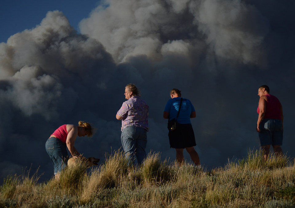 Photo - Residents watch as the Black Forest Fire burns northeast of Colorado Springs, Colo, Tuesday, June 11, 2013. The fire burned several homes and forced the evacuation of thousands of people. (AP Photo/Bryan Oller)