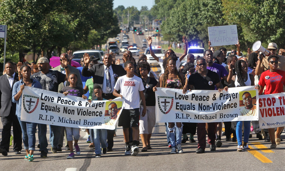 Photo - A march organized by area ministers makes its way down W. Florissant in Ferguson, Mo. on Wednesday, Aug. 13, 2014. On Saturday, Aug. 9, 2014, a white police officer fatally shot Michael Brown, an unarmed black teenager, in the St. Louis suburb. (AP Photo/St. Louis Post-Dispatch, J.B. Forbes)