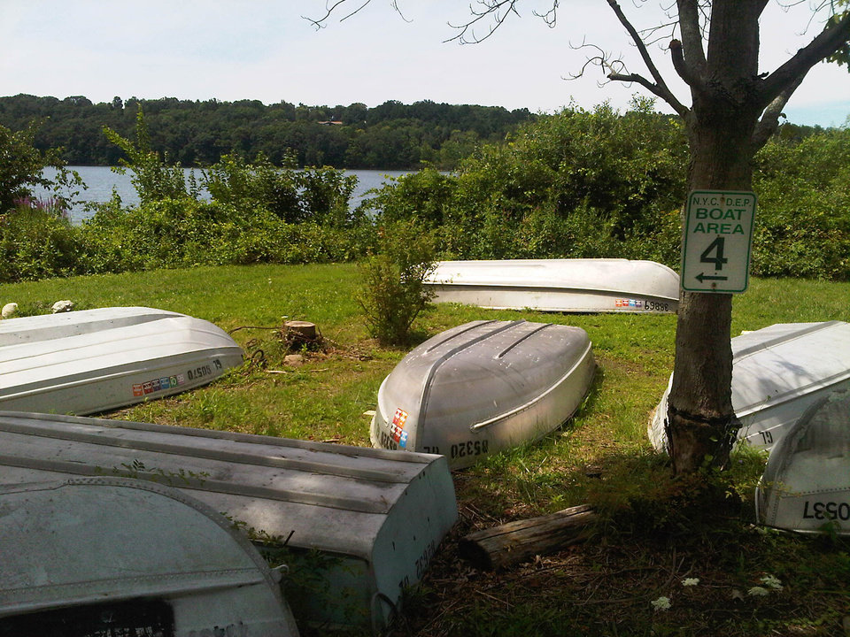 Photo -   Rowboats sit on the shore of Lake Gleneida in Carmel, New York, Tuesday Aug. 7, 2012, where a woman drowned, and and a 6-year-old clinging to the floating corpse was rescued by three people fishing in a rowboat. Authorities said an autopsy was planned to determine if the woman drowned or suffered some kind of medical emergency while wading with the girl in the water. (AP Photo/Jim Fitzgerald)