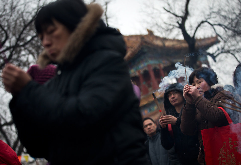 Temple goers burn incense while praying on the first day of Chinese Lunar New Year at Yonghegong Lama Temple in Beijing, Sunday, Feb. 10, 2013. Millions across China are celebrating the arrival of the Lunar New Year, the Year of the Snake, marked with a week-long Spring Festival holiday. (AP Photo/Andy Wong)