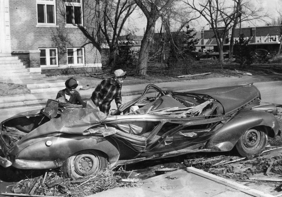 No one knows  where it came from, or to who it belongs, or how it got in this condition.  Tommy Lamarr, 11, and Orley Spoke 12, inspect this damage auto after the famous Woodward tornado. 4/9/1947
