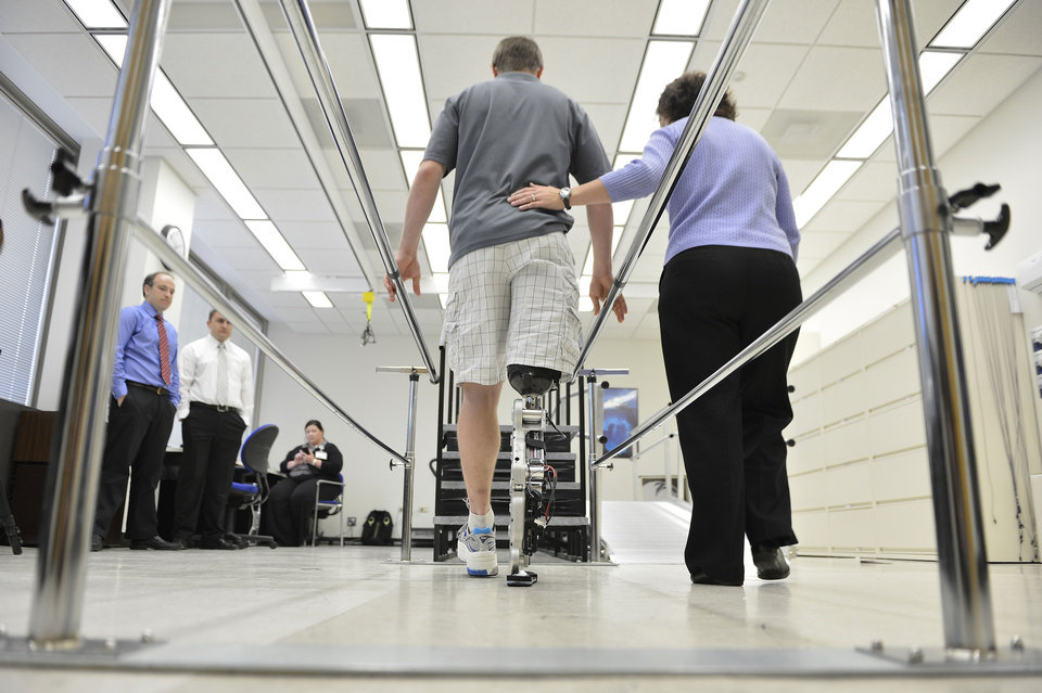 Physical therapist assistant Suzanne Finucane, right, helps Zac Vawter as he practices walking with an experimental