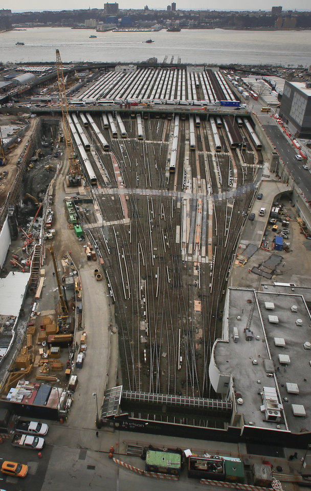 Photo - This photo of the Hudson Yards shows parked Long Island Rail Road trains with ongoing construction nearby, Thursday April 17, 2014 in New York. The construction of a $15 billion Hudson Yards project will fill 28 acres between the Hudson River and Tenth Avenue with six skyscrapers, after completely covering the train yards with a platform foundation. (AP Photo/Bebeto Matthews)