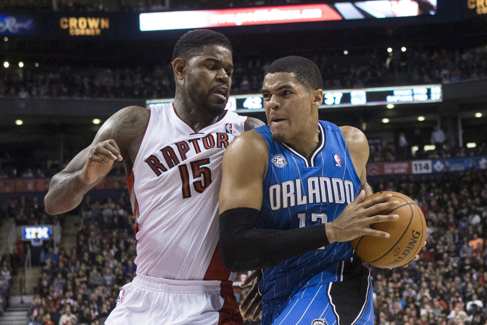 Photo - Orlando Magic's Tobias Harris, right, drives at Toronto Raptors' Amir Johnson during the first half of an NBA basketball game in Toronto, Sunday, Feb. 23, 2014. (AP Photo/The Canadian Press, Chris Young)