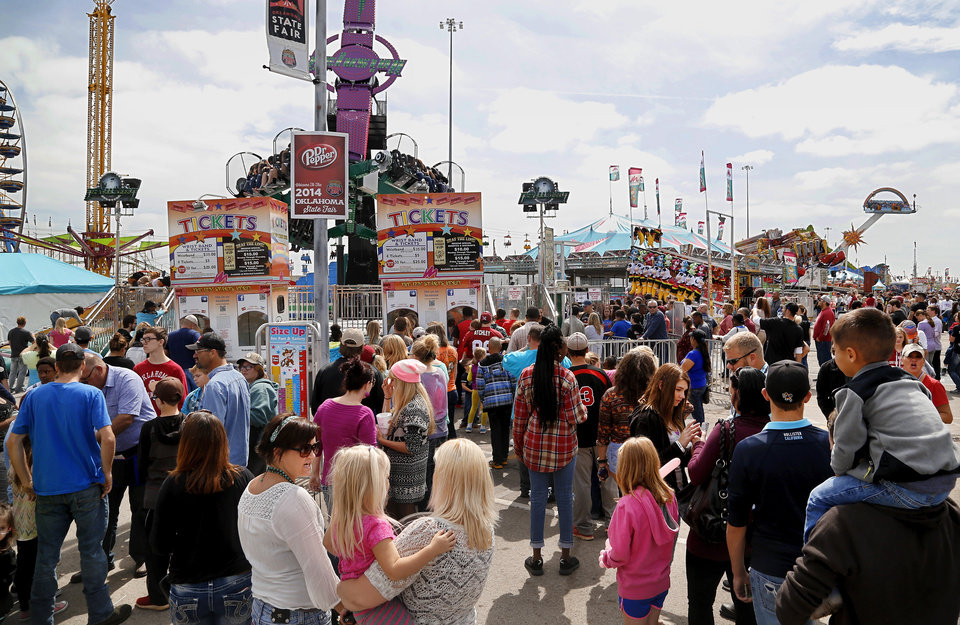 Photo -  Visitors to the 2014 Oklahoma State Fair wait in long lines to purchase tickets and armbands for midway attractions on the first weekend of the fair. [Photo by Jim Beckel, The Oklahoman]