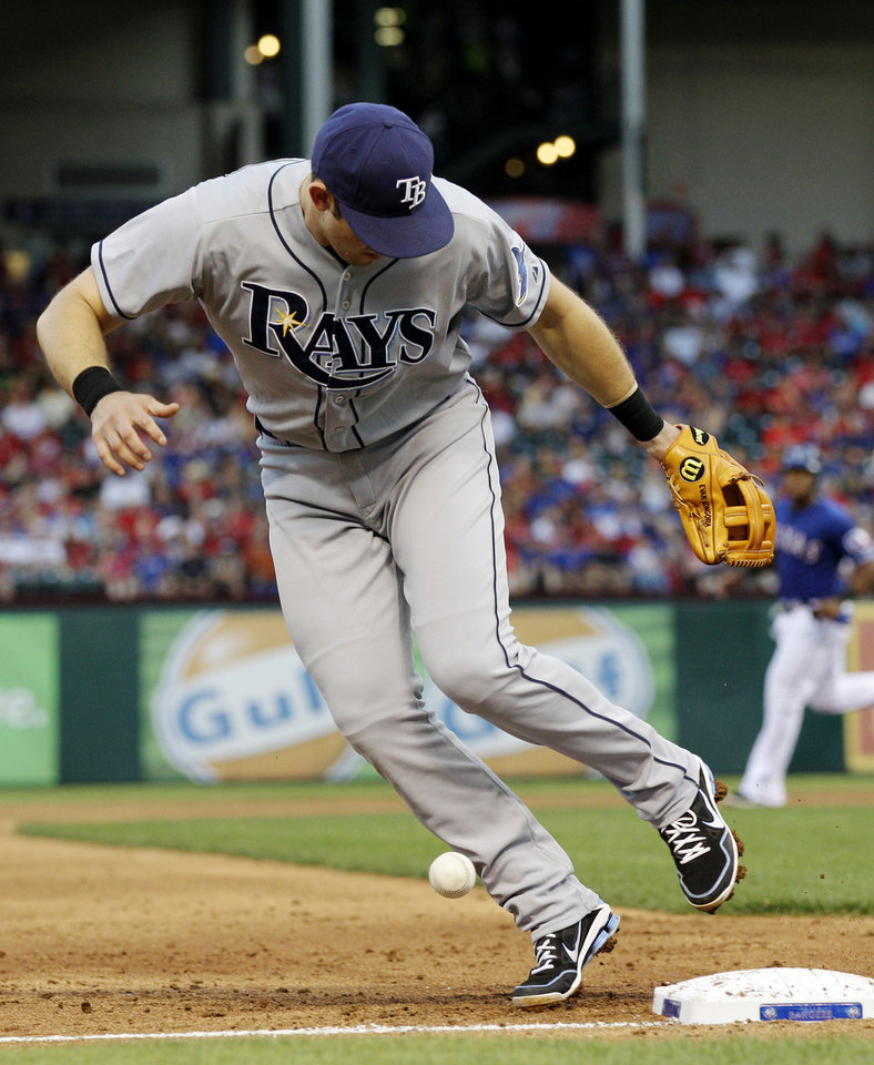 Photo -   Tampa Bay Rays third baseman Evan Longoria watches a ball hit by Texas Rangers' Michael Young bounce over the bag and stay fair in the first inning of a baseball game, Friday, April 27, 2012, in Arlington, Texas. Young was safe at first on the hit. (AP Photo/Tony Gutierrez)