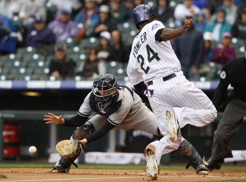Photo - New York Yankees catcher Chris Stewart, left, fields the throw from the outfield as Colorado Rockies' Dexter Fowler scores on a sacrifice fly hit by Carlos Gonzalez in the first inning of a baseball game in Denver on Thursday, May 9, 2013. (AP Photo/David Zalubowski)