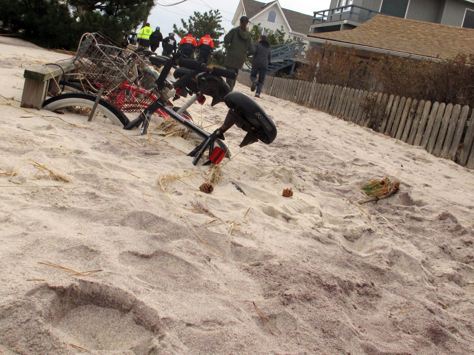 Photo -   In this Friday, Nov. 16, 2012 photo, bicycles remain buried beneath several feet of sand in the Fire Island community of Kismet, N.Y. In the background, Suffolk County and other officials tour the community damaged from Superstorm Sandy. (AP Photo/Frank Eltman)