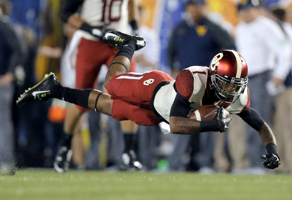 Photo - Oklahoma's K.J. Young (1) falls to the ground after making a catch during the college football game between West Virginia  Mountaineers and the University of Oklahoma Sooners at Milan Puskar Stadium in Morgantown, W.Va., Saturday, Sept. 20, 2014. Photo by Sarah Phipps, The Oklahoman