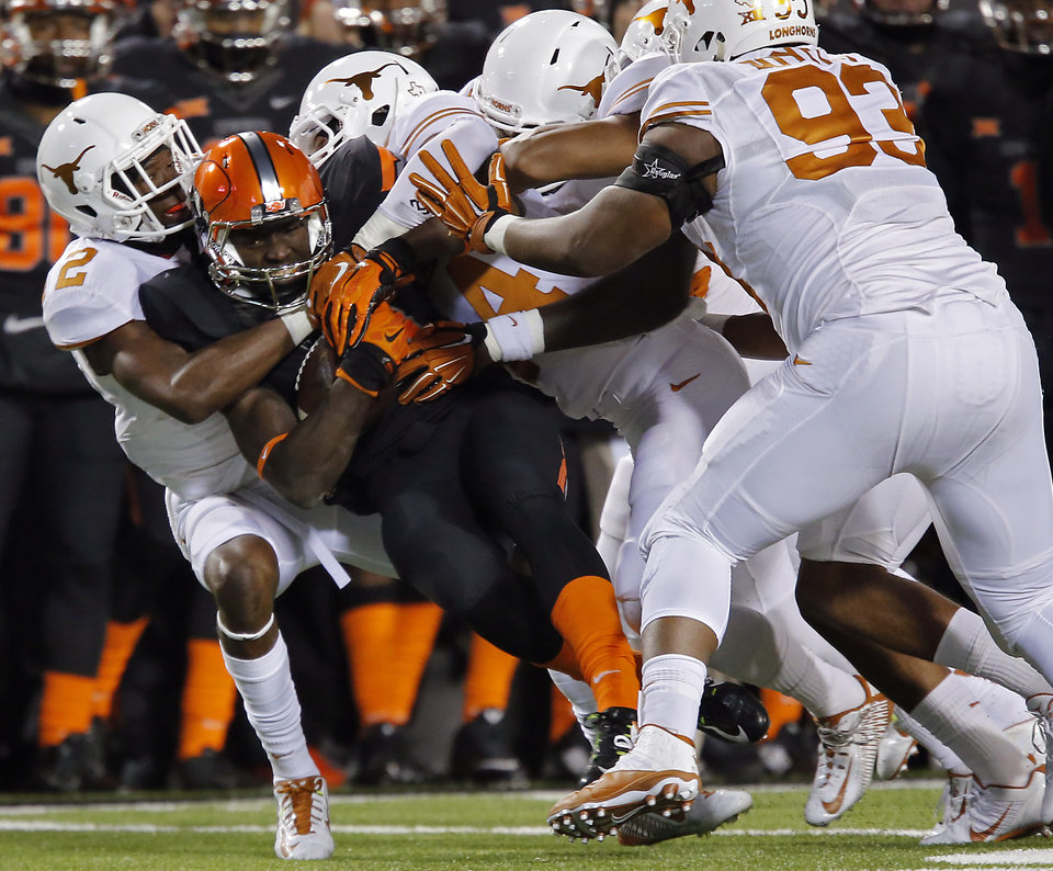 Photo - Oklahoma State's James Washington (28) is brought down by the Texas defense during the college football game between the Oklahoma State University Cowboys (OSU) the University of Texas Longhorns (UT) at Boone Pickens Staduim in Stillwater, Okla. on Saturday, Nov. 15, 2014.  Photo by Chris Landsberger, The Oklahoman