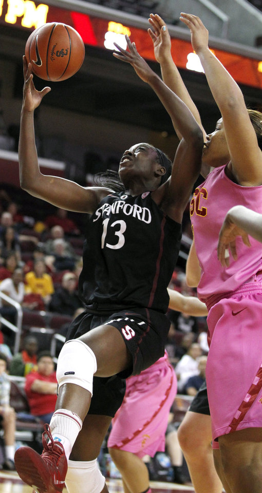 Photo - Stanford forward Chiney Ogwumike (13) pulls down a rebound against Southern California forward Deanna Calhoun, right, during the first half of an NCAA college basketball game Friday, Feb. 21, 2014, in Los Angeles. (AP Photo/Alex Gallardo)