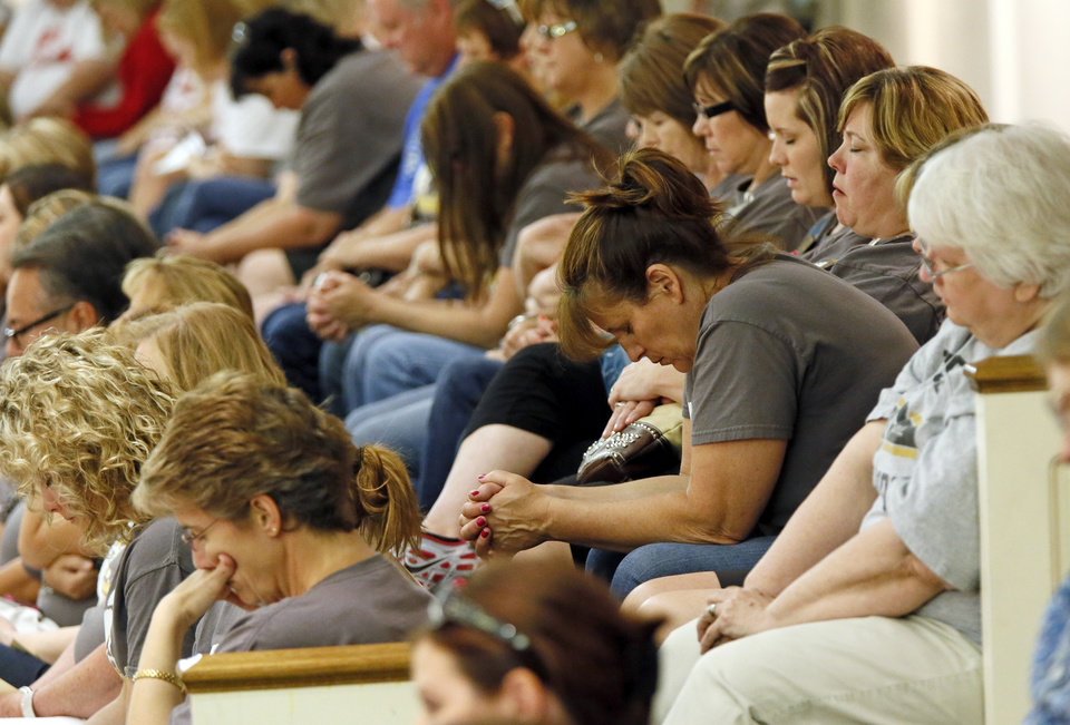 People pray at the beginning of a district-wide meeting of Moore Public Schools employees at Southern Hills Baptist Church, 8601 Pennsylvania Ave., in Oklahoma City, Wednesday, May 22, 2013, after a tornado struck south Oklahoma City and Moore, Okla., on Monday. Photo by Nate Billings, The Oklahoman