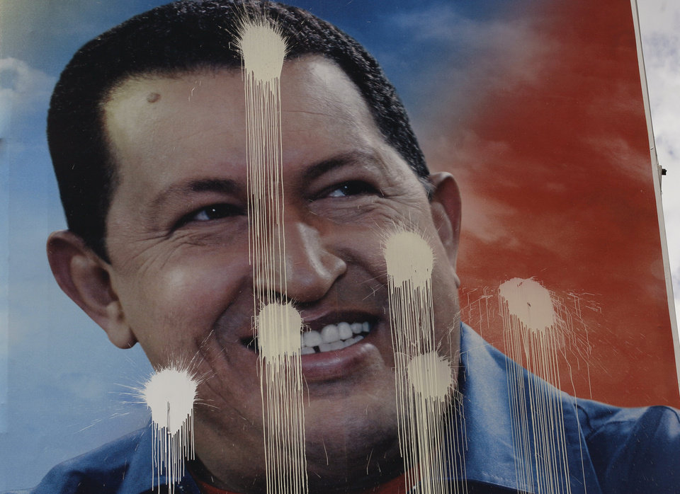 A defaced election campaign poster of Venezuela's President Hugo Chavez hangs in Caracas, Venezuela, Saturday, Oct. 6, 2012. Venezuelans will head to the polls Sunday to vote in their country's presidential election, deciding on whether to keep Chavez or seek change. (AP Photo/Fernando Llano)