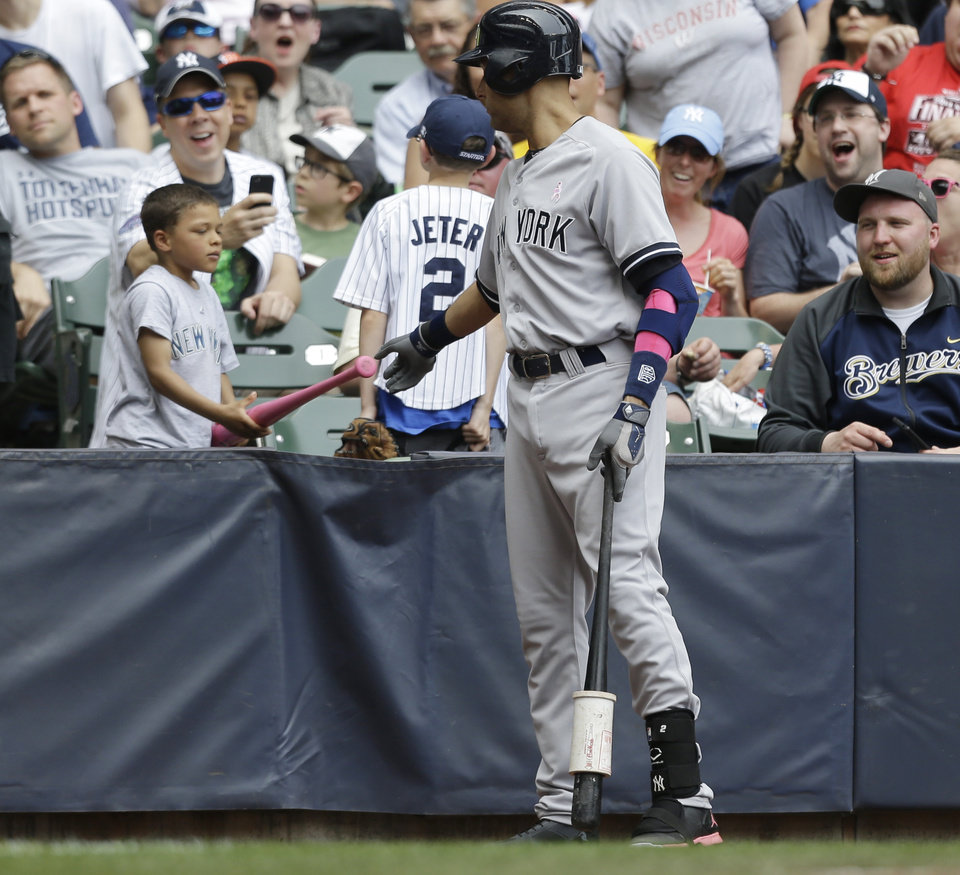 Photo - New York Yankees' Derek Jeter gives a pink bat to a small boy while waiting to bat in the fourth inning of a baseball game against the Milwaukee Brewers Sunday, May 11, 2014, in Milwaukee. (AP Photo/Jeffrey Phelps)