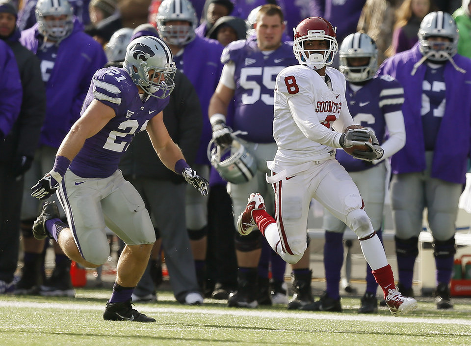 Oklahoma's Jalen Saunders (8) runs past Kansas State's Jonathan Truman (21) after a reception during an NCAA college football game between the Oklahoma Sooners and the Kansas State University Wildcats at Bill Snyder Family Stadium in Manhattan, Kan., Saturday, Nov. 23, 2013. Oklahoma won 41-31. Photo by Bryan Terry, The Oklahoman