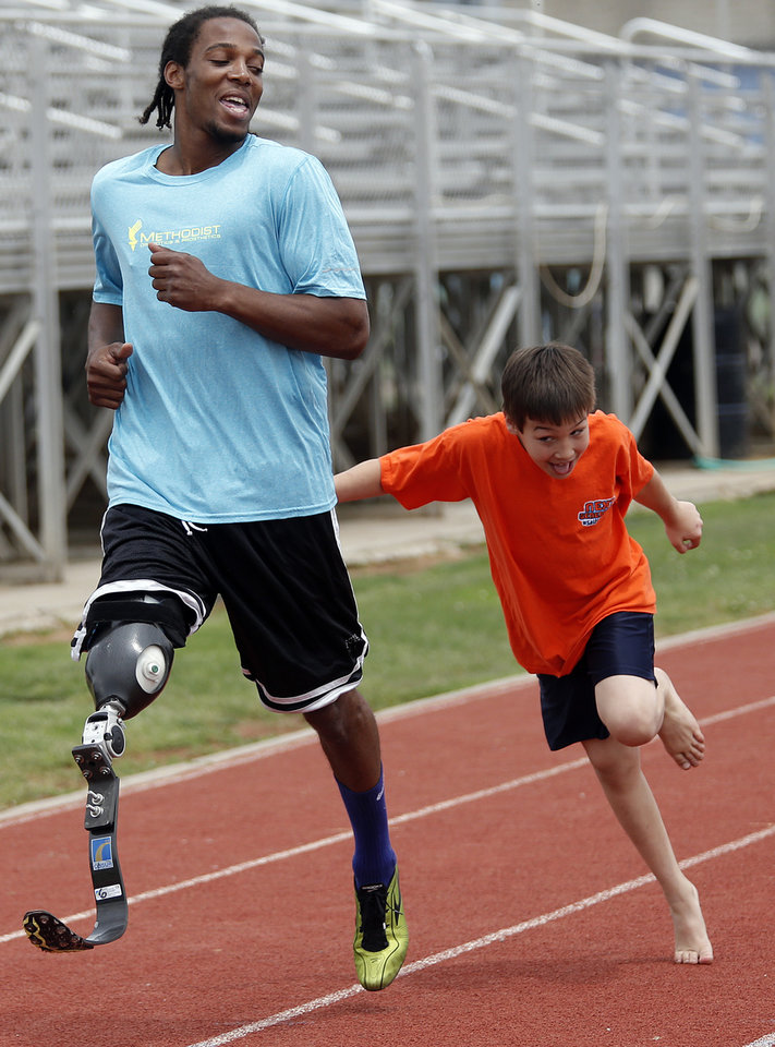 Landon Camp, 9, of Mississippi, tries to keep up with Shaquaille Vance, of Mississippi, while running on the track during the opening day of activities for the Endeavor Games at Edmond North High School on Thursday, June 6, 2013 in Edmond, Okla. Photo by Chris Landsberger, The Oklahoman
