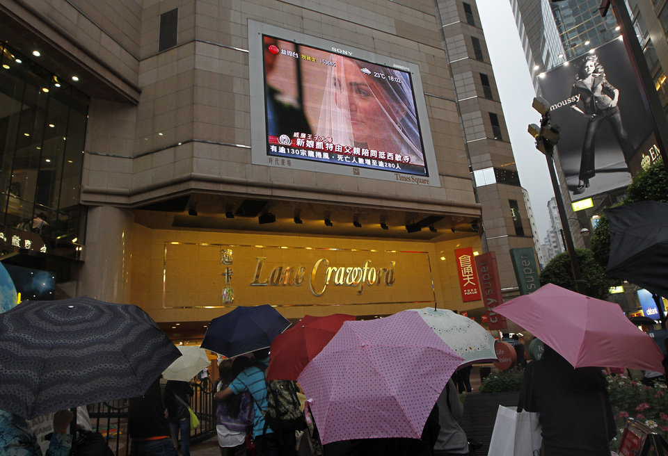 Photo - Hong Kong people watch the Royal Wedding of Prince William and Kate Middleton on a huge TV at Time Square in the former British colony on Friday, April 29, 2011. (AP Photo/Vincent Yu) ORG XMIT: XVY104