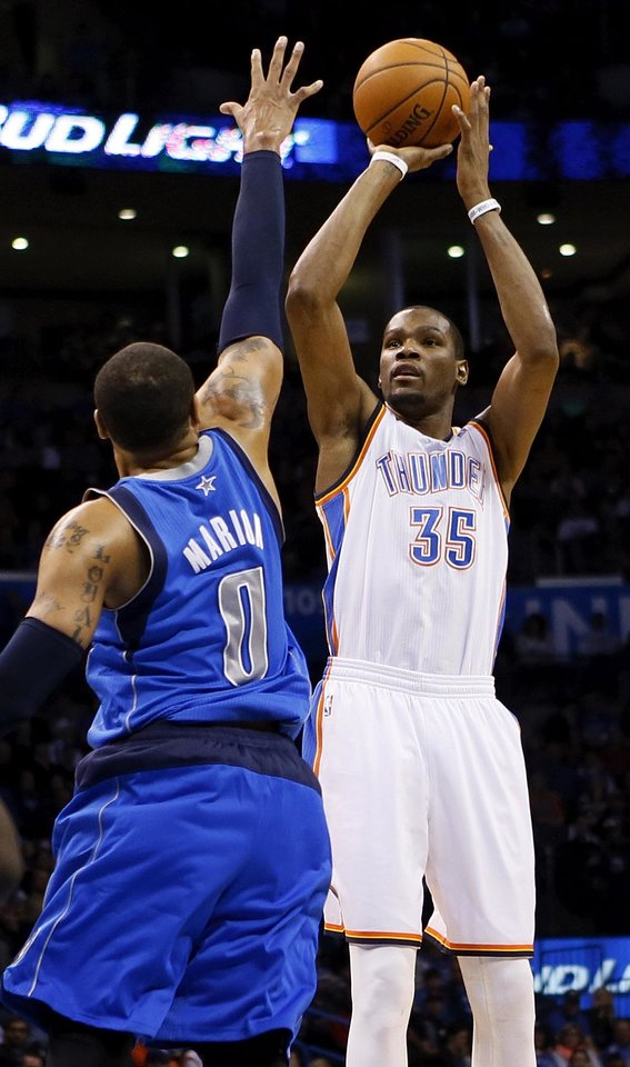 Photo - Oklahoma City's Kevin Durant (35) shoots against Dallas' Shawn Marion (0) during an NBA basketball game between the Oklahoma City Thunder and the Dallas Mavericks at Chesapeake Energy Arena in Oklahoma City, Sunday, March 16, 2014. Photo by Nate Billings, The Oklahoman