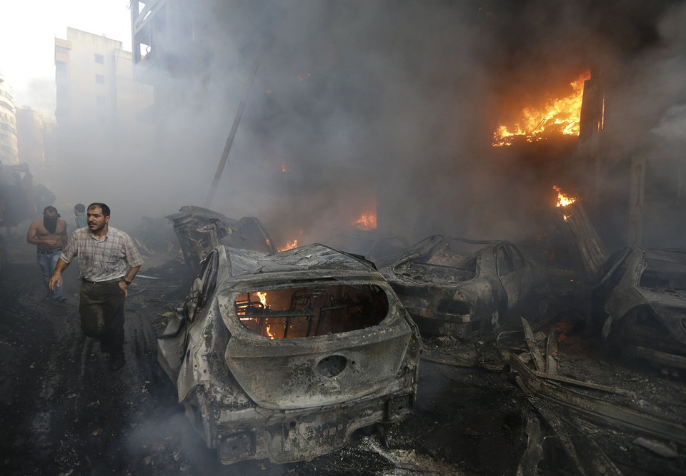 Photo - Lebanese citizens run past a burned cars and shops at the site of a car bomb explosion in southern Beirut, Lebanon, Thursday Aug. 15, 2013. The powerful car bomb ripped through a southern Beirut neighborhood that is a stronghold of the militant group Hezbollah on Thursday, killing at least three people and trapping others in burning buildings, the media said. (AP Photo/Hussein Malla)