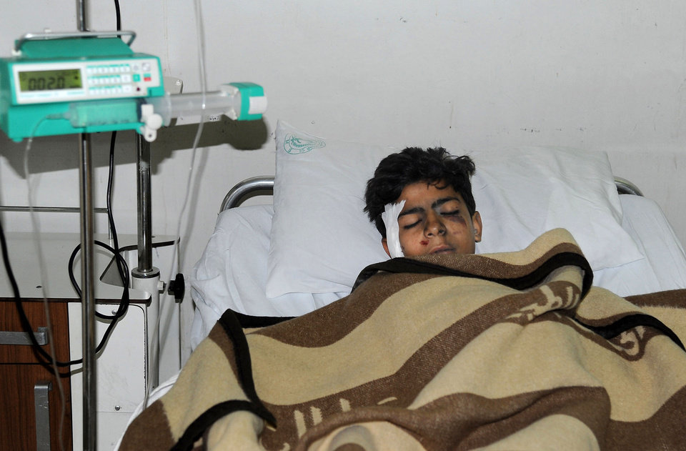 In this photo released by the Syrian official news agency SANA, an injured Syrian student, lies at a hospital bed after he was wounded when a mortar hit the al-Batiha school in al-Wafideen camp, about 25 kilometers (15 miles) northeast of Damascus, Syria, Tuesday Dec. 4, 2012. A mortar slammed into a ninth-grade classroom in the Damascus suburbs on Tuesday, killing 29 students and a teacher, according to state media, as the civil war closed in on President Bashar Assad\'s seat of power. (AP Photo/SANA)