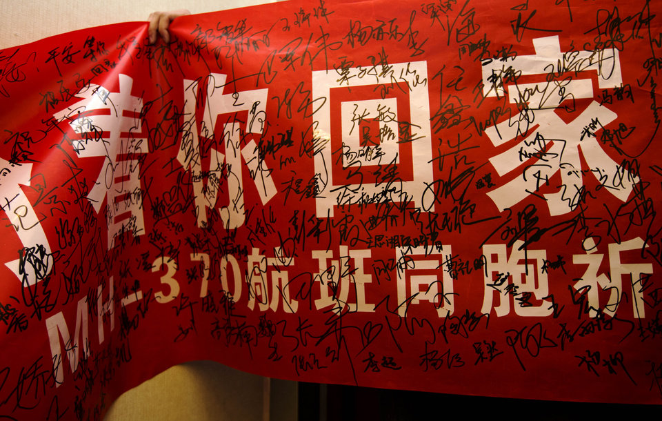Photo - A Chinese university student displays a banner that reads: