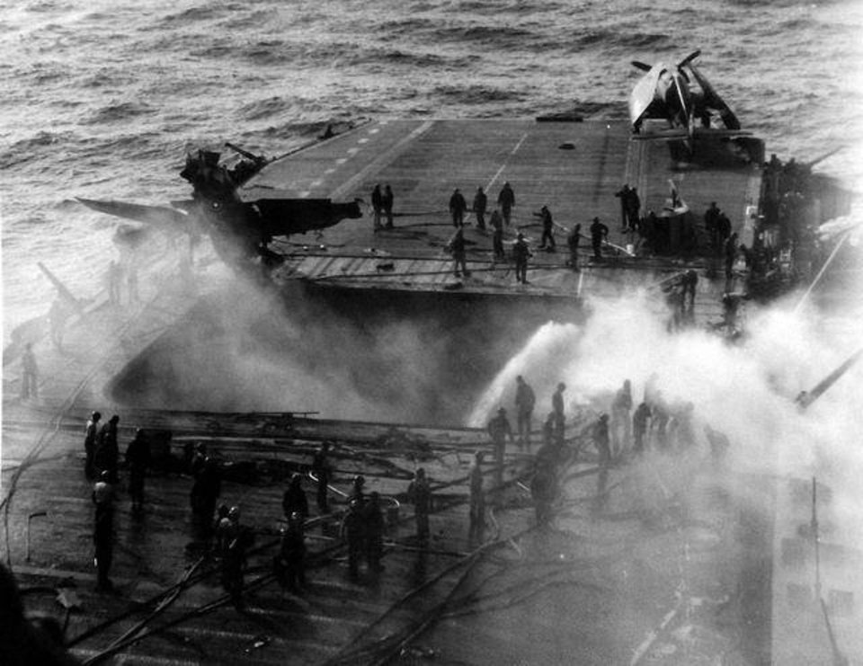 Photo -  Crew inspect the damage from a kamikaze attack that crippled the USS Enterprise in May 1945. Roy Wright, 91, of northwest Oklahoma City, was on deck when the Japanese Zero struck the carrier. [National Archives photo]