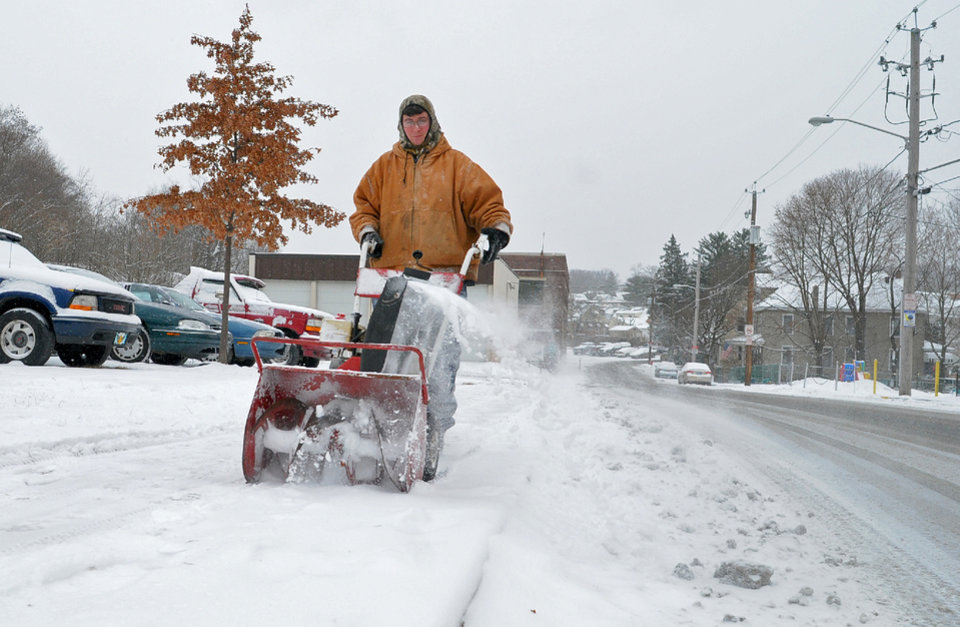 Photo - Tom Gerber, of Schuylkill Haven, Pa., clears snow from a sidewalk at the Neighborhood Recreation Center in Schuylkill Haven, Pa., Tuesday, Jan. 21, 2014. The National Weather Service has issued a winter storm warning for Tuesday's storm with public schools closed in parts of central Pennsylvania and elsewhere.    (AP Photo/ The Republican-Herald, Andy Matsko) MANDATORY CREDIT