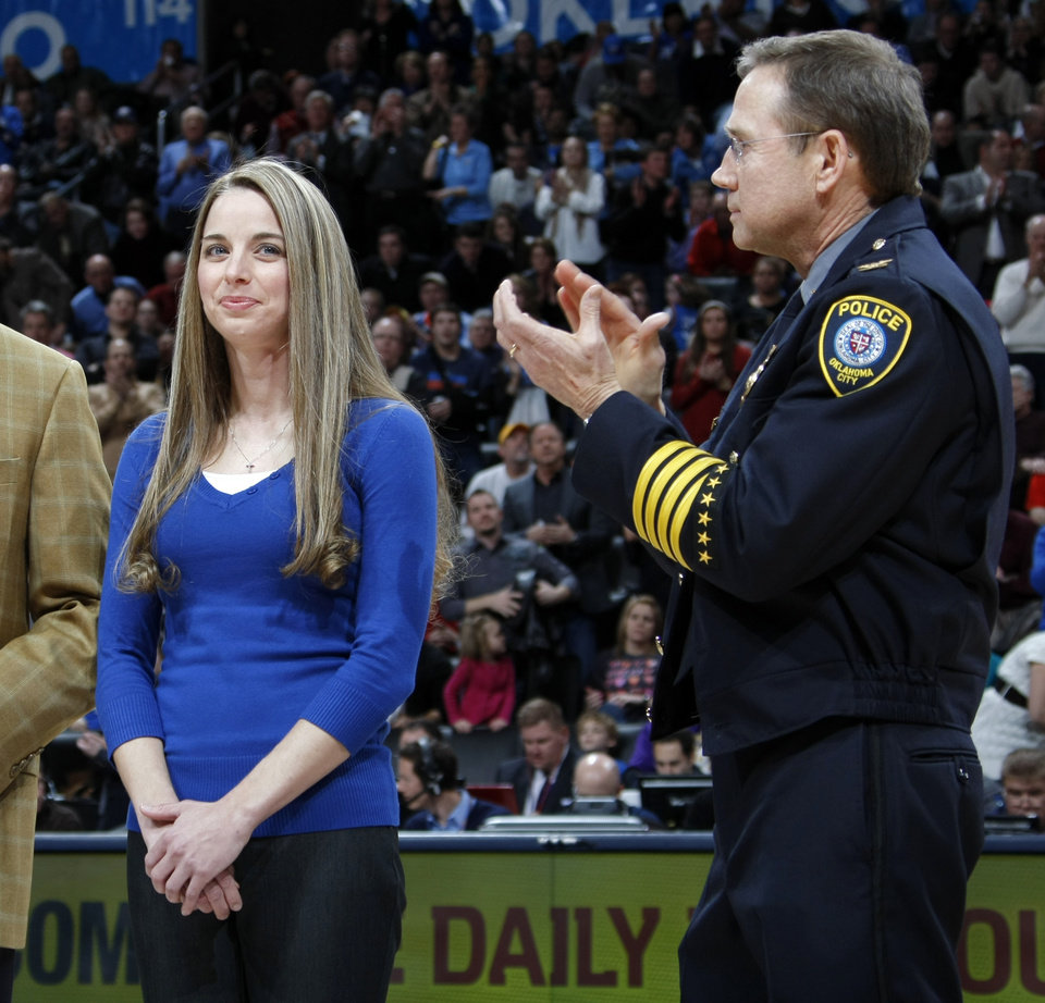 Photo - Oklahoma City police chief Bill Citty, right, applauds as Oklahoma City police officer Katie Lawson is recognized with the Devon Energy Community Hero Award during the NBA basketball game between the Orlando Magic and Oklahoma City Thunder in Oklahoma City, Thursday, January 13, 2011. Photo by Nate Billings, The Oklahoman