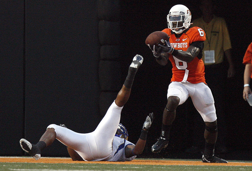 Photo - Oklahoma State cornerback Andrew McGee (6) catches a interception over  Trae Johnson (1) during the college football game between the University of Tulsa (TU) and Oklahoma State University (OSU) at Boone Pickens Stadium in Stillwater, Oklahoma, Saturday, September 18, 2010. Photo by Sarah Phipps, The Oklahoman